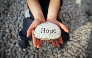 "• Child's hands holding up a stone with ""hope"" written on it"